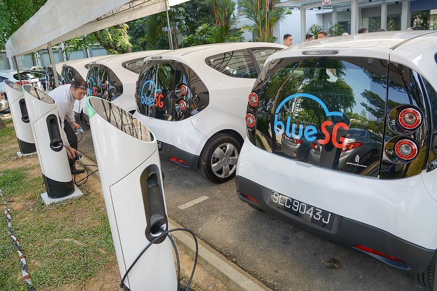 A man is seen at the charging point behind a BlueSG electric car.