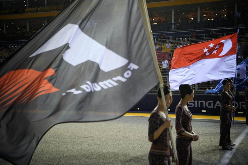 Singapore Airlines grid girls hold flags at the starting line ahead of the 2017 Formula One Singapore Airlines Singapore Grand Prix at the Marina Bay street circuit on Sept 17, 2017.