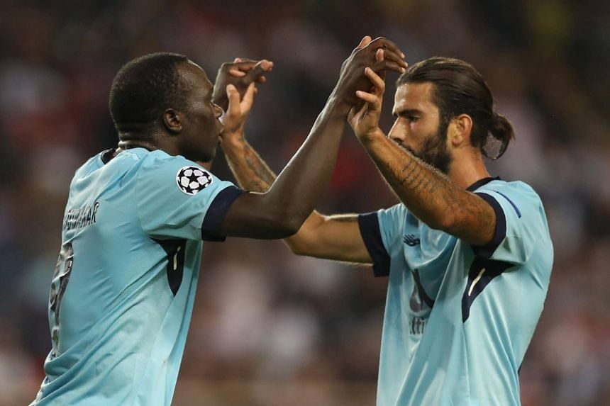 Porto's Cameroonian forward Vincent Aboubakar celebrates with Portuguese midfielder Sergio Oliveira after scoring a goal during the Uefa Champions League game against Monaco on Sept 26, 2017.