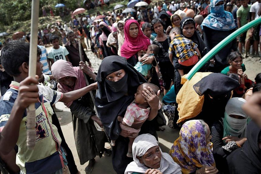 Rohingya refugees wait to receive aid in Cox's Bazar, Bangladesh, on Sept 27, 2017.