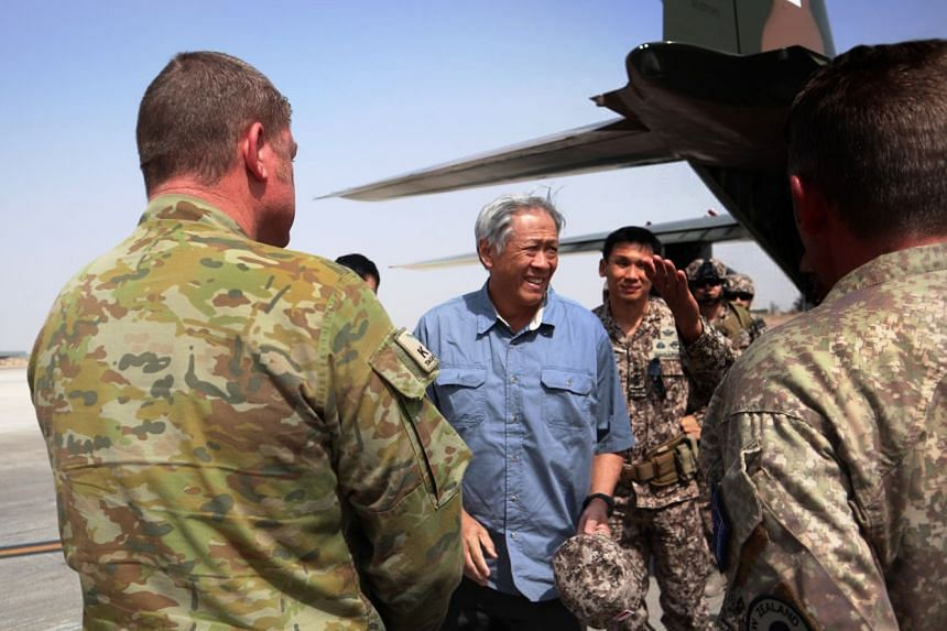 Dr Ng Eng Hen being received by officers from the Australian Defence Force, the New Zealand Defence Force and the Singapore Armed Forces.