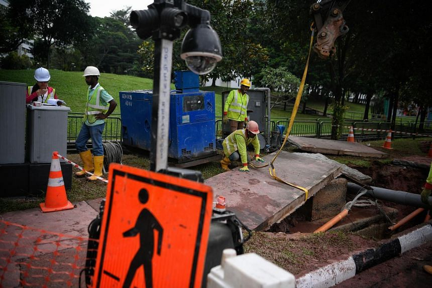 Workers secure a harness to a concrete slab for removal as repair works get under way at the site of the burst pipe at the junction of Bukit Batok West Ave 6 and Bukit Batok West Ave 8, on Sept 27, 2017.