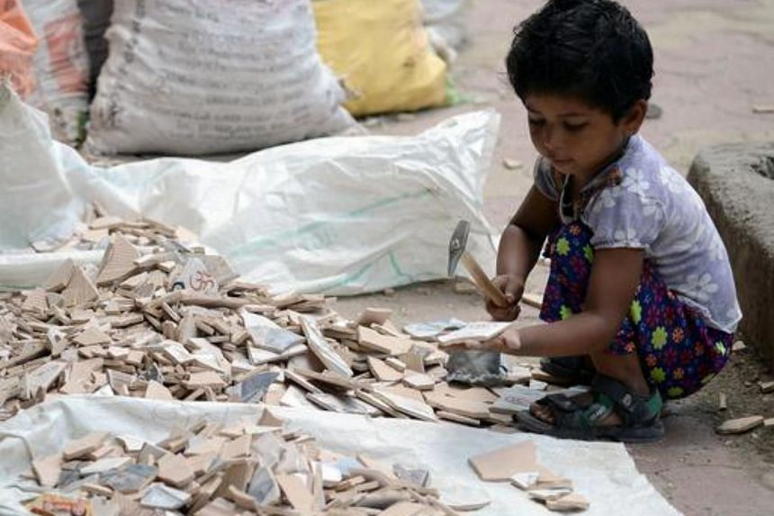 An Indian child breaks apart broken tiles alongside her mother outside an under-construction apartment building in Mumbai.