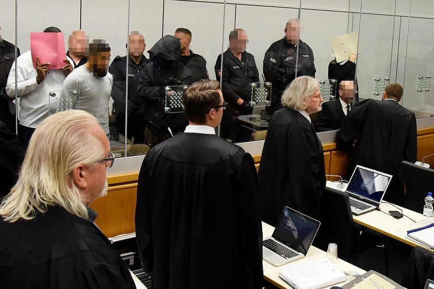 Defendant Ahmad Abdulaziz Abdullah A. (right), also known as Abu Walaa, and co-defendants arrive for the first day of his trail at the higher regional court (Oberlandesgericht, OLG) in Celle, Germany, on Sept 25, 2017.