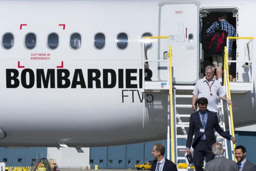 Attendees exit the new Bombardier CS100 airplane during an event at the company's facility in Toronto, Canada, on Sept 10, 2015.