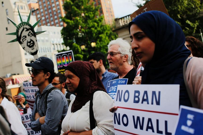 People take part in a rally in New York to protest the restrictive guidelines issued by the US on who qualifies as a close familial relationship under the Supreme Court order on the Muslim and refugee ban.