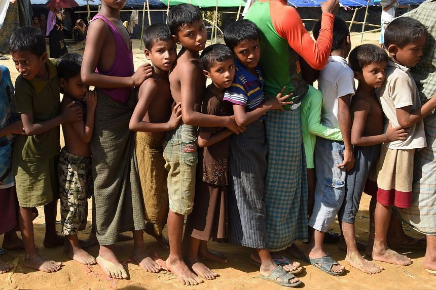 Children lining up relief supplies at the Kutupalong refugee camp for Rohingyas who have fled to Bangladesh to escape violence in Myanmar, on Sept 22, 2017.