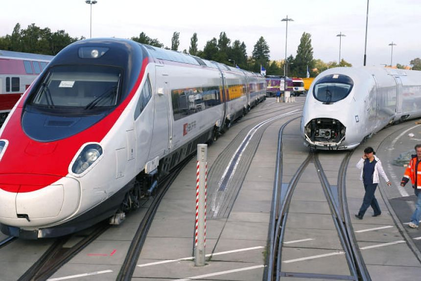 Workers walk past an Alstom Pendolino high-speed train, left, and a Siemens Velaro high-speed train in Berlin, Germany, on Sept 18, 2010.