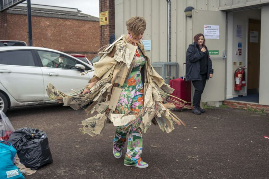 A delighted Ms Shelley Bolderson with a coat made from the pages of a book. She bought the coat at Royal Shakespeare Company's sale of costumes.