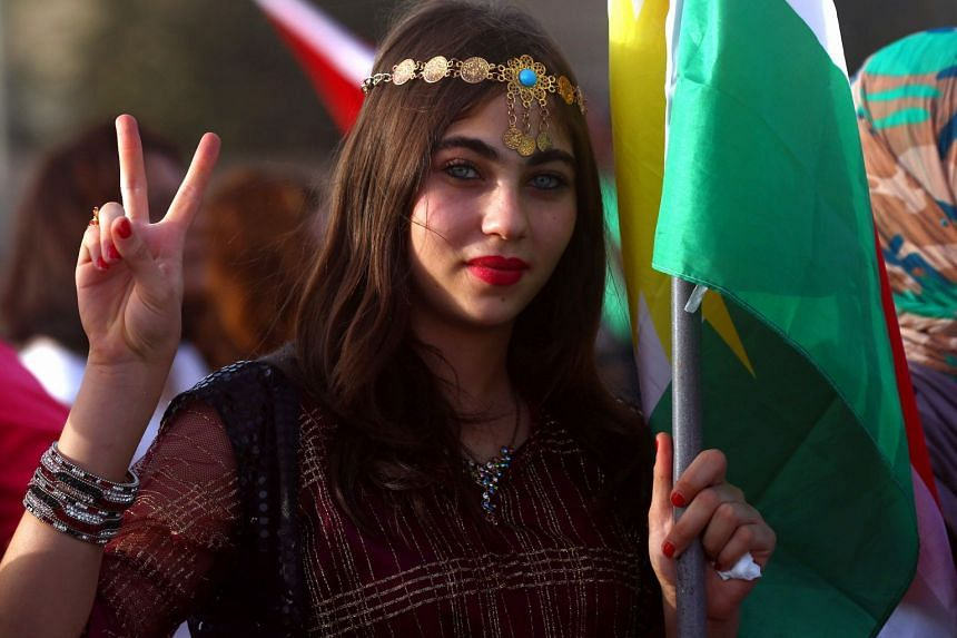 A Syrian Kurd shows her support for the independence referendum at a gathering in the northeastern Syrian city of Qamishli.