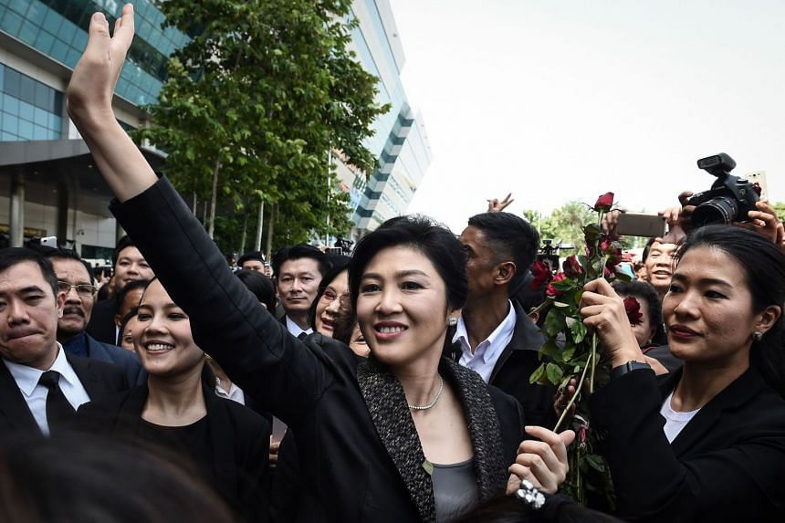 Former Thai prime minister Yingluck Shinawatra waves to supporters as she leaves the Supreme Court in Bangkok, on Aug 1, 2017.