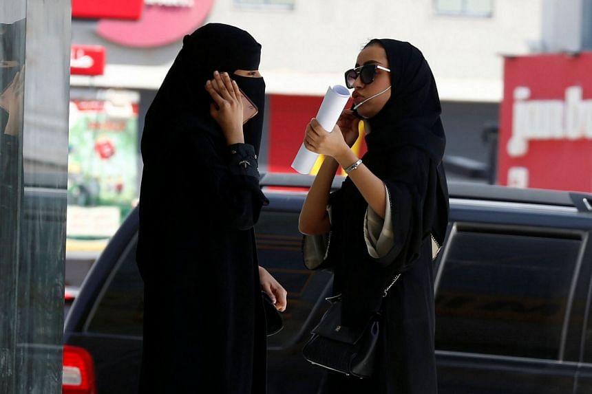 Saudi women speak on phones in Riyadh, Saudi Arabia, Sept 27, 2017.