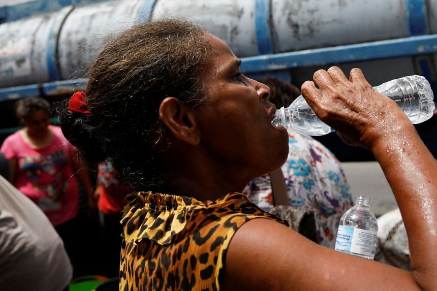 A woman drinks from a bottle after filling it with water from a tank truck.