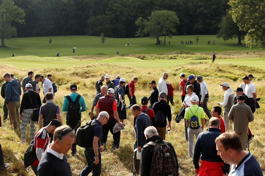 Northern Ireland's Rory McIlroy looks for his ball with spectators during the first round.