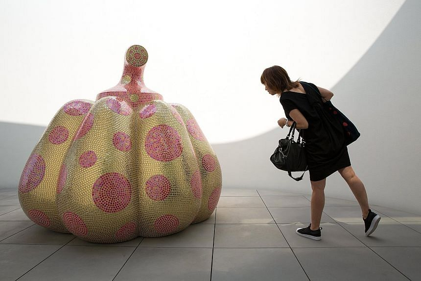 A visitor looking at the sculpture titled Starry Pumpkin by Yayoi Kusama, known for her polka dots and pumpkins, during a media preview of the museum in Tokyo on Tuesday.