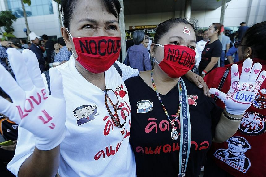 Supporters of former Thai prime minister Yingluck Shinawatra in front of the Supreme Court yesterday expressing their love for the ousted leader. The court found her guilty of negligence over her government's rice subsidy scheme, which is said to hav
