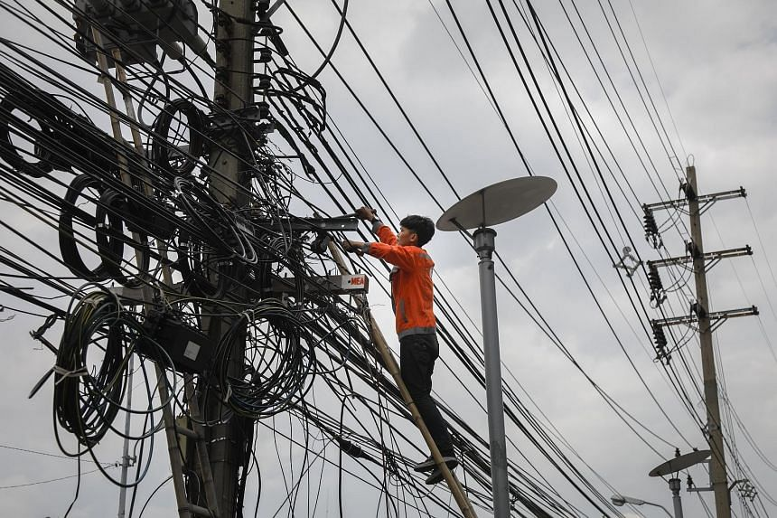 A worker cutting a mass of cluttered power lines in Bangkok as the Thai capital prepares to move its cables underground to improve the look of the city and also as a precaution against the concrete power poles collapsing onto the street. Thailand's C