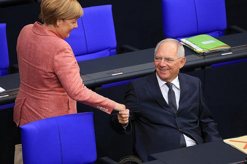 Mr Wolfgang Schaeuble with Chancellor Angela Merkel in the Bundestag on Sept 6. His 45 years in the Bundestag make him Germany's longest-serving lawmaker.