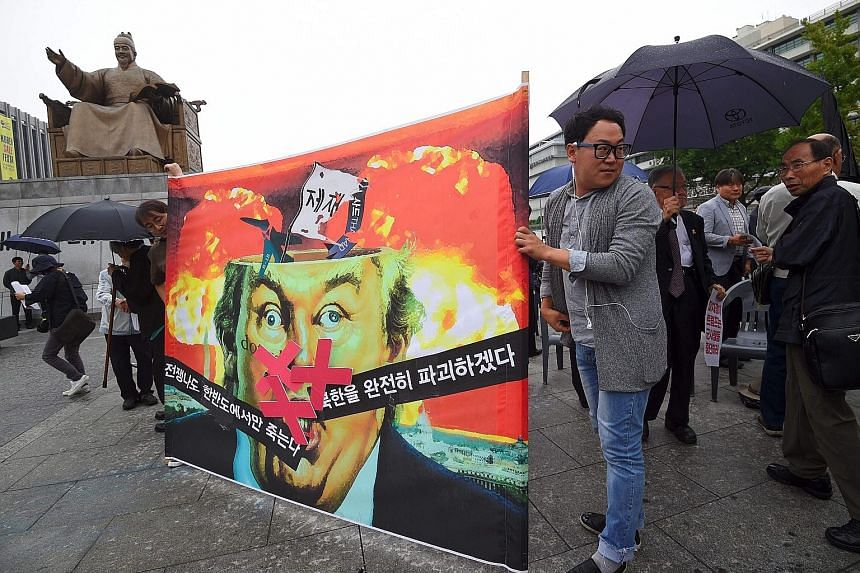 "Anti-war activists displaying a banner showing a caricature of US President Donald Trump during an anti-Trump rally near the US Embassy in Seoul yesterday. The Korean script on the banner reads ""If war breaks out, only those on the Korean peninsula w"
