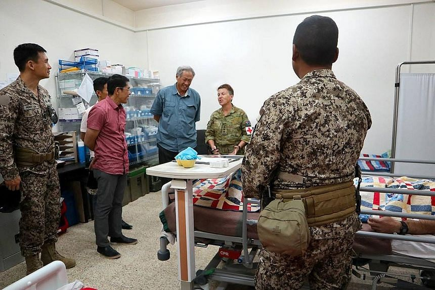 Defence Minister Ng Eng Hen, with (from left) Chief of Defence Force Perry Lim and Senior Minister of State for Defence Maliki Osman, visiting the Singapore Armed Forces medical team at the coalition camp in Iraq on Tuesday.