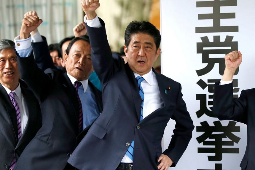 Japan's Prime Minister Shinzo Abe (centre) and his party's lawmakers pledge to win in the upcoming lower house election, at their party headquarters in Tokyo on Sept 28, 2017.