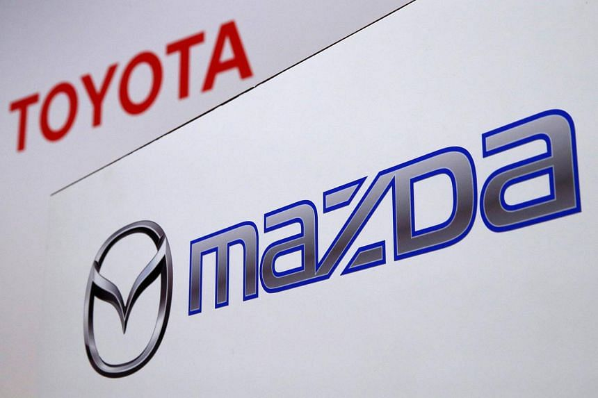 The logos of Toyota Motor and Mazda Motor are pictured before the companies' joint news conference in Tokyo on Aug 4, 2017.