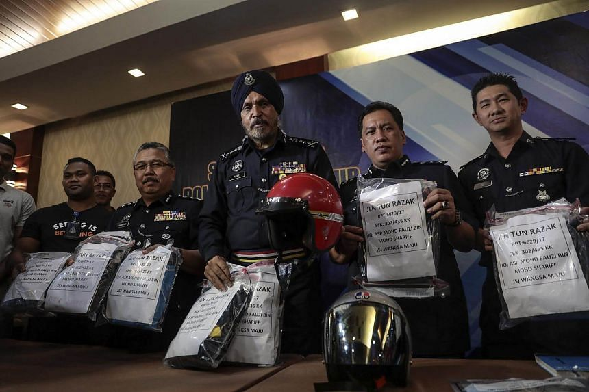Kuala Lumpur Police Chief Amar Singh Ishar Singh (centre) holds bags containing evidence from the suspects during a press conference at Kuala Lumpur Police Headquarters, on Sept 16, 2017.