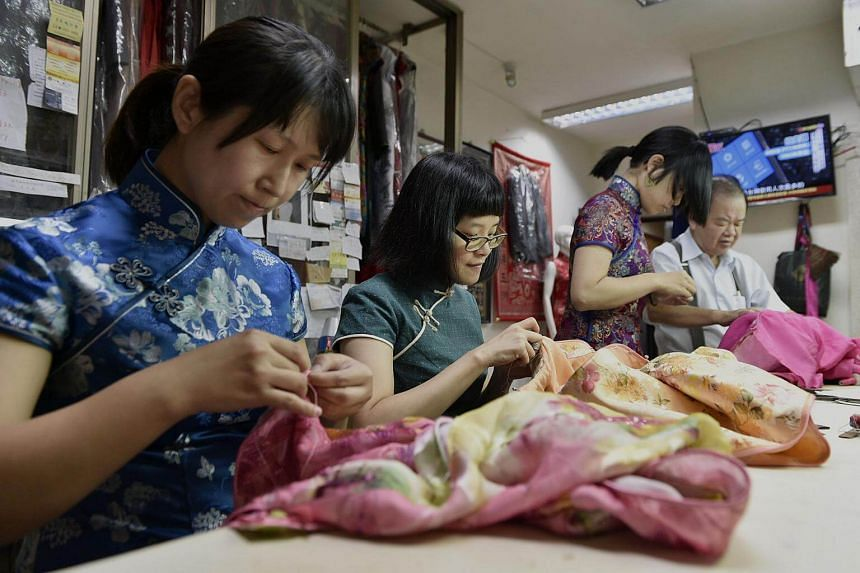 "Taiwanese ""qipao"" maker Lin Chin-te (far right) working with students at his studio in Taipei, on Aug 30, 2017."