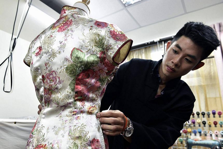 """Taiwanese """"qipao"""" maker Lee Wei-fan checking his work at his studio in Taipei, on Aug 29, 2017."""