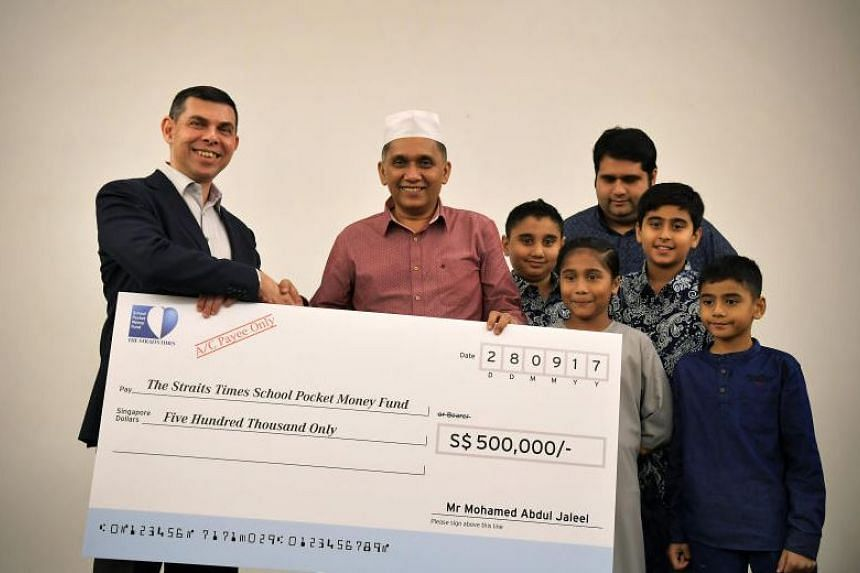 Mr Mohamed Abdul Jaleel (second from left), founder and chief executive officer of Mini Environment Service Group, presented The Straits Times editor Warren Fernandez (left) with a cheque for a $500,000 donation at The Straits Times School Pocket Mon