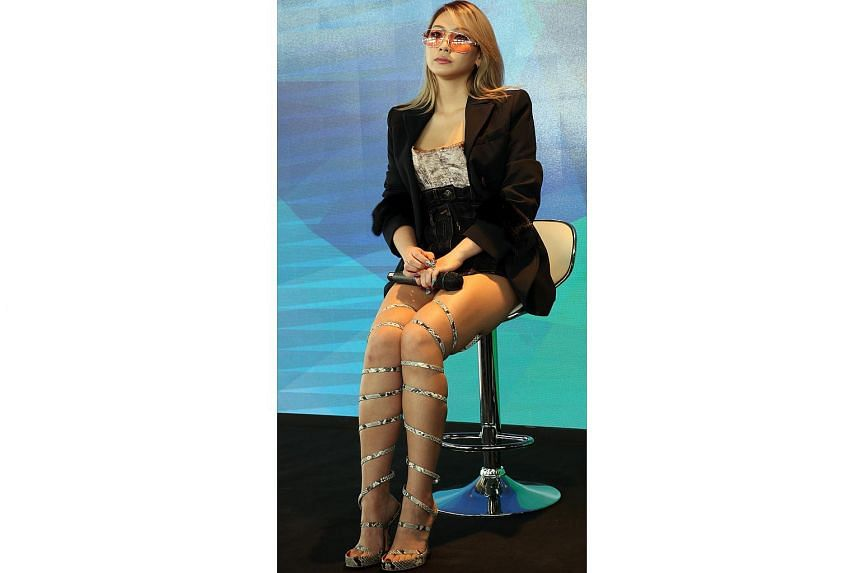 At a press conference, CL wore a bustier outfit and heeled sandals that coiled around her legs like vines.