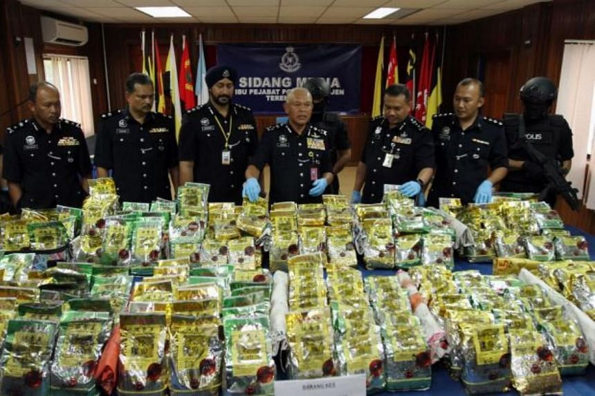 Malaysian police officers displaying the haul of syabu, valued at about about RM22million (S$7 million).