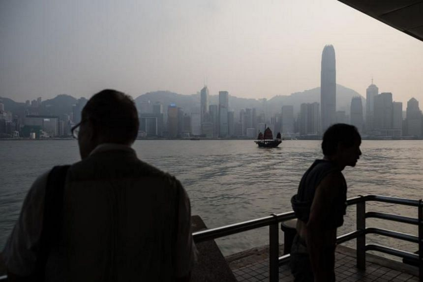 Tourists riding a traditional junk boat in front of the Hong Kong city skyline on Sept 17, 2017.