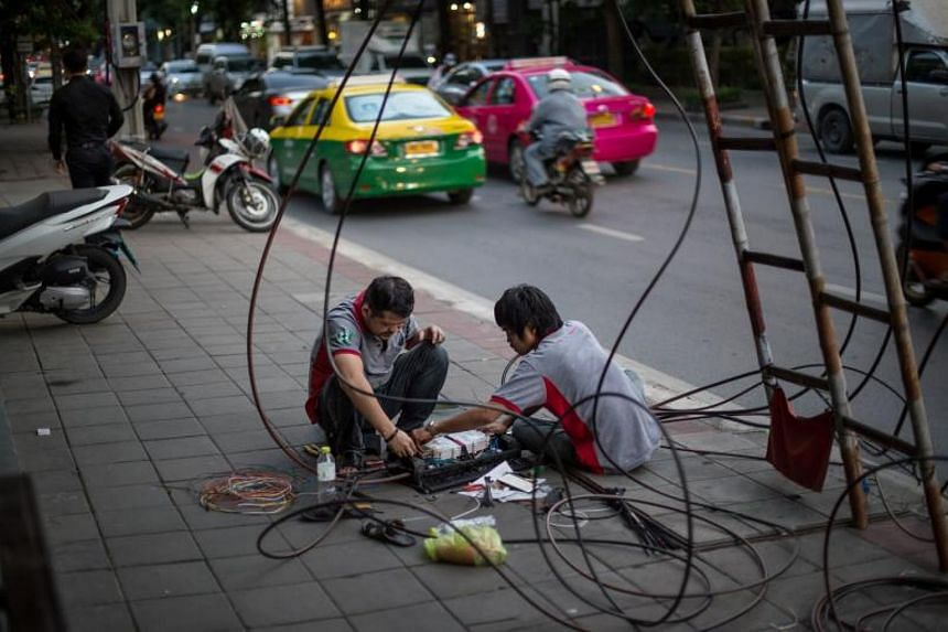 Two internet company workers troubleshoot a problem with a network relay box at a neighborhood in Bangkok. A smart city is one that integrates the Internet and communication technology with the Internet of Things (IoT).
