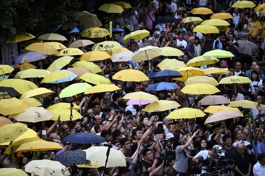Protesters holding up yellow umbrellas during a gathering to mark the third anniversary of pro-democracy protests in Hong Kong on Sept 28, 2017.