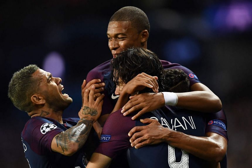 PSG's Cavani (front) is congratulated by team mates Mbappe (top) and Alves after he scored.