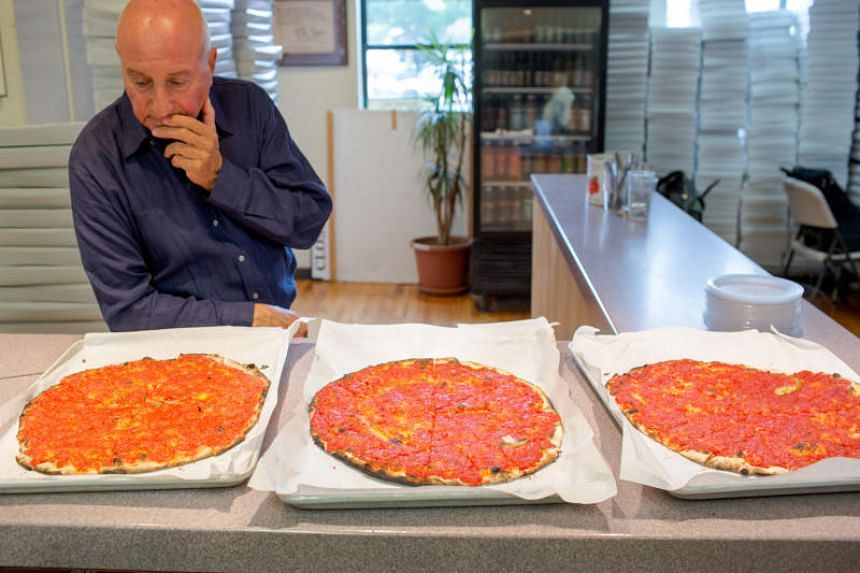 At Frank Pepe Pizzeria Napoletana in New Haven, Connecticut, Mr Francis Rosselli inspects the fresh pizzas made with the three final tomato sauce options during the pizzeria chain's annual tomato tasting in New Haven, Connecticut, on Sept 21, 2017.