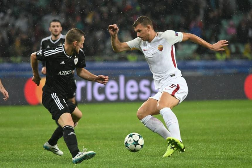 Qarabag's Maksim Medvedev (left) and Roma's Edin Dzeko vie for the ball during the Champions League Group C match in Baku on Sept 27, 2017.