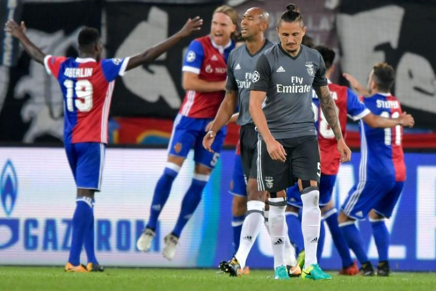 Benfica's Luisao and Ljubomir Fejsa (foreground) wear dejected looks as Basel's players celebrate a goal during the Champions League Group A match at St. Jakob-Park Stadium in Basel on Sept 27, 2017.