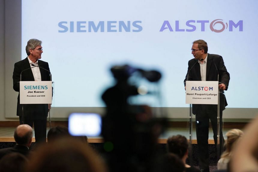 German ICE train manufacturing company Siemens President and CEO, Joe Kaeser (left) and French railway transport company Alstom CEO, Henri Poupart-Lafarge announcing the union between Alstom and Siemens at a press conference in Paris, on Sept 27, 201