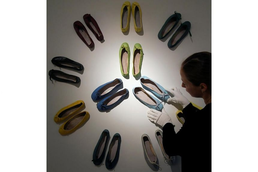 An employee adjusts a display of ballet pumps belonging to Audrey Hepburn at Christie's in central London, Britain, on Sept 22, 2017.