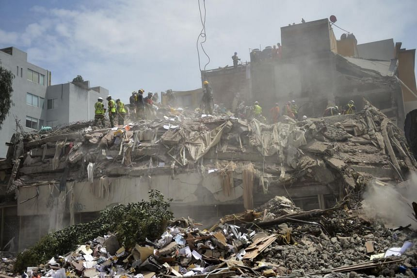 Rescuers work in a building toppled by a magnitude 7.1 quake that struck central Mexico almost a week ago, in Mexico City, on Sept 25, 2017.
