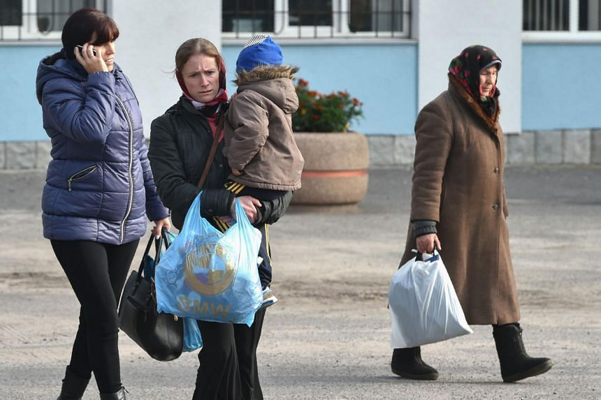 Residents leave during the evacuation of the town of Kalynivka following explosions at a nearby arms depot, on Sept 27, 2017.