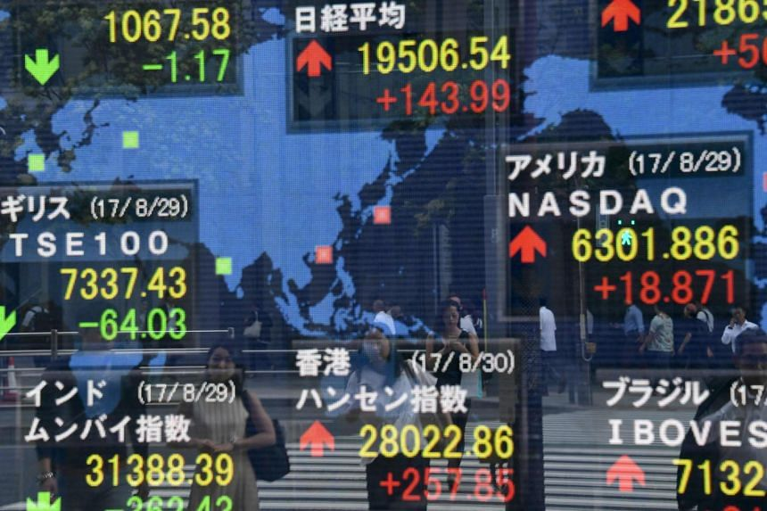 Pedestrians are reflected on an electronic stock indicator at the window of a securities company in Tokyo, on Aug 30, 2017.