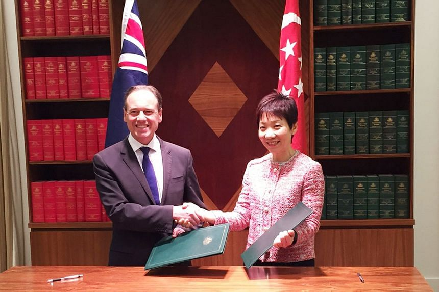 Australia's Minister of Sport Greg Hunt and Singapore's Minister for Community, Culture and Youth Grace Fu exchanging documents after signing a three-year memorandum of understanding (MOU) on sports cooperation yesterday in Melbourne. The MOU aims to
