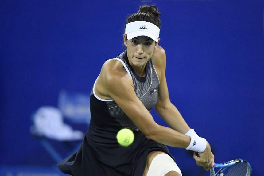 Muguruza hits a return against Magda Linette of Poland.