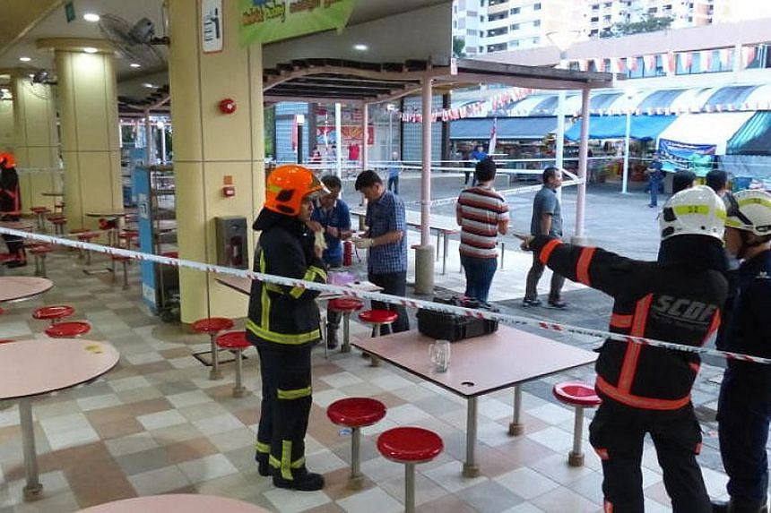 Singapore Civil Defence Force officers at the Ang Mo Kio hawker centre where the pipe-shaped object landed. An area the size of a football field was cordoned off for six hours, with more than 50 police officers at the scene.