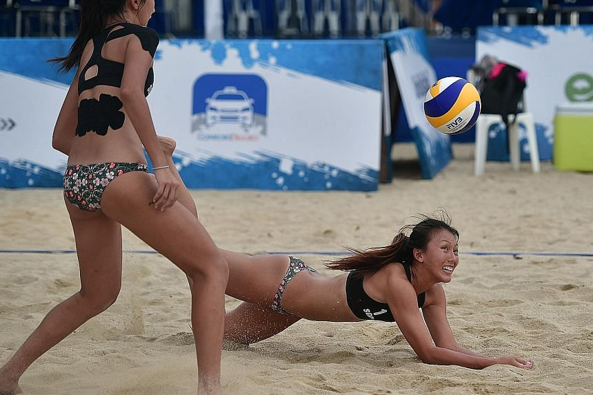 Singapore's Ong Wei Yu dives while teammate Serene Ng looks on during their 21-14, 21-6 victory against Laos' Mitta Vatthana and Phouthuksa Keovixay at yesterday's South-east Asian Beach Volleyball Championships at Palawan Beach, Sentosa.