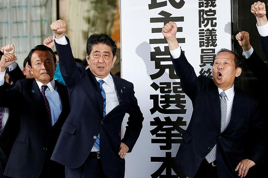 Above: Japanese Prime Minister Shinzo Abe and his party's lawmakers, including Mr Taro Aso (left) and Mr Toshihiro Nikai (right), pledging to emerge victorious in the upcoming Lower House elections at the LDP's headquarters in Tokyo yesterday.