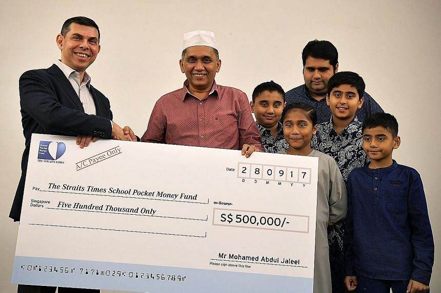 Mr Warren Fernandez, chairman of The Straits Times School Pocket Money Fund, receiving a donation of $500,000 from Mini Environment Service Group founder and CEO Mohamed Abdul Jaleel yesterday. With them were Mr Jaleel's son Mohamed Jinna and grandch